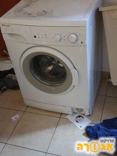 מכונת כביסה עובדת עם נזילה בניקוז וכפתור